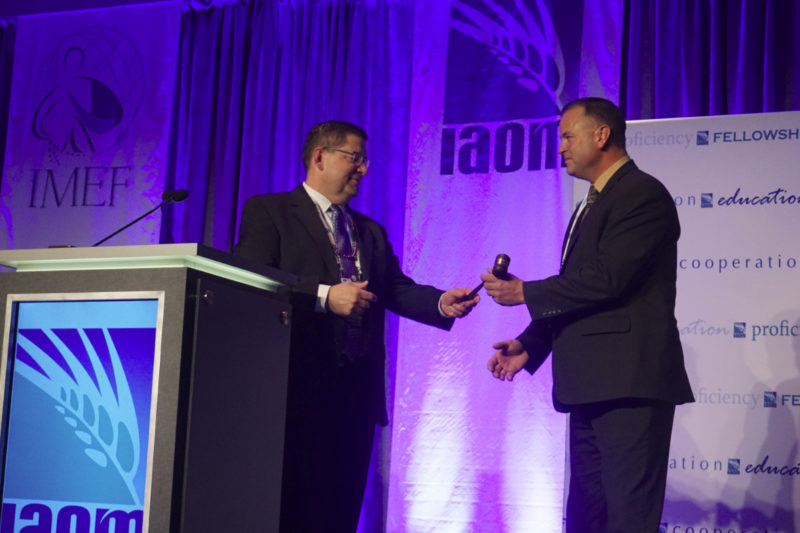 Outgoing IAOM President Jeff Hole, left, hands the gavel to incoming-president, David Jansen, right.